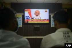 FILE - Journalists watch as India's Prime Minister Narendra Modi addresses the nation, at a journalist club in Siliguri, India, Oct. 20, 2020.