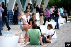 People wait for news at a family reunification center, after a wing of a 12-story beachfront condo building collapsed, June 24, 2021, in the Surfside area of Miami.