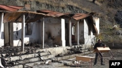 A man carries a table near a destroyed house in the country side outside the town of Kalbajar on November 23, 2020. - Azerbaijan said on November 20, 2020, its troops entered a district bordering Nagorno-Karabakh handed back by Armenian separatists…