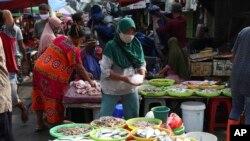 Seorang pedagang ikan mengenakan masker di tengah pandemi corona di sebuah pasar di Jakarta, 24 Juni 2020. (Foto: dok).