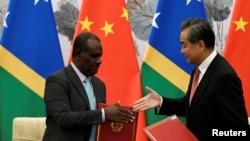 Ủy viên Quốc vụ Trung Quốc Vương Nghị bắt tay Bộ trưởng Ngoại giao Quần đảo Solomon Jeremiah Manele trong một buổi lễ đánh dấu việc thiết lập quan hệ ngoại giao giữa hai nước.