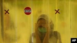 9일 인도네시아 자카르타에서 여성이 백화점에 들어서기 전 전신소독을 받고 있다.