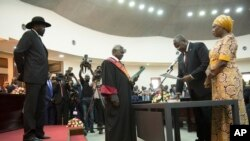 FILE - South Sudan's President Salva Kiir Mayardit, left, swears in Dr. Riek Machar as the first vice president of the country, in Juba, Feb. 22, 2020.