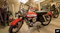 FILE - Marty Rosenblum, a historian for Harley Davidson, points to Elvis Presley's first motorcycle in a storage room at the Milwaukee-based motorcycle company, Wisconsin, Oct. 16, 1995.