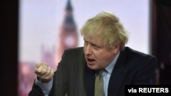 Britain's Prime Minister Boris Johnson gestures on BBC TV's The Andrew Marr Show in London, Britain, Jan. 3, 2021. Picture taken through glass. (Jeff Overs/BBC/Handout via Reuters)