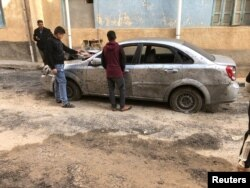 FILE - Libyan boys check a damaged car after a shell fell on a residential area at Hadba al-Badri district, in Tripoli, Libya, Jan. 28, 2020.