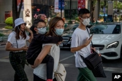FILE - Chinese family wearing face masks walk in a pedestrian crossing in Bangkok, Thailand, Jan. 29, 2020.