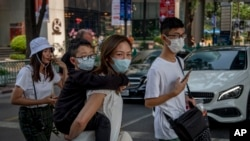 Chinese family wearing face masks walk in a pedestrian crossing in Bangkok, Thailand, Wednesday, Jan. 29, 2020. Tourism Council of Thailand said Tuesday that new coronavirus outbreak estimated to cost 50 billion Bhat (1,613,892 US Dollars) in lost…