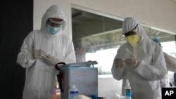 Trabajadores de la salud se preparan para tomar muestras para detectar COVID-19, en el Parque Deportivo Cocodrilos en Caracas, Venezuela, el sábado 19 de septiembre de 2020.