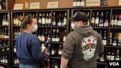 Sara Robinet i njen suprug kupuju vino u prodavnici UnWind u Aleksandriji. (Foto: VOA/Debra Blok)