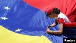 Una partidaria del líder opositor venezolana Juan Guaidó, fija una bandera durante un mitin contra el gobierno del presidente venezolano Nicolás Maduro en Caracas. Abril 6, 2019.