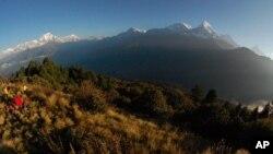 Para pendaki menyaksikan matahari terbit di Pegunungan Annapurna (kanan) di Nepal tengah.