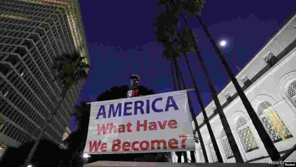 """미 상원에서 트럼프 탄핵안이 기각된 후 캘리포니아주 로스앤젤레스에서 남성이 상원의 결정에 항의하는 시위를 하고 있다. 시위자가 든 플래카드에는 """"미국, 우리가 어떻게 된 것인가?""""가 적혀 있다."""