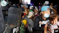 Pasukan keamanan Guatemala (kiri) memblokir perbatasan untuk menghalangi rombongan migran Honduras memasuki negara itu, Minggu (17/1).