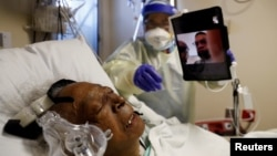 Florence Bolton, 86, a coronavirus disease (COVID-19) positive patient, lies in her intensive care bed as family members attempt to FaceTime her at Roseland Community Hospital on the South Side of Chicago, Illinois, Dec. 1, 2020.