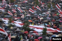 People take cover from rain under umbrellas during an opposition rally to protest against police brutality and to reject the presidential election results in Minsk, Belarus, Sept. 6, 2020.