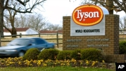 FILE - A car passes in front of a Tyson Foods Inc. sign at Tyson headquarters in Springdale, Ark., Jan. 29, 2006.