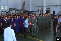 Taiwan President Tsai Ing-wen, center left, poses for photos with airmen near a Taiwan Indigenous Defense Fighter jet displayed during a visit to the Penghu Magong military air base in outlying Penghu Island, Taiwan, Sept. 22, 2020.