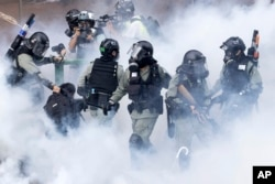 FILE - Police in riot gear move through a cloud of smoke as they detain a protester at the Hong Kong Polytechnic University.