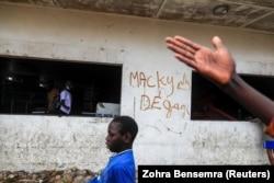 """Un garçon passe devant un graffiti sur un mur d'un supermarché Auchan saccagé, sur lequel on peut lire """"Macky dégage"""", à Dakar, Sénégal, le 5 mars 2021."""
