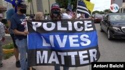 """Una mujer sostiene una bandera con el mensaje """"La vida de los policías importan"""" en inglés. Foto: [Antoni Belchi,VOA]"""