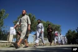 FILE - Afghan Taliban prisoners walk after being released from Bagram Prison, in Parwan province, Afghanistan, May 26, 2020.