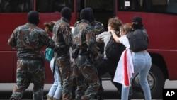 FILE - Masked men detain students during a protest against official presidential election results, in Minsk, Belarus, Sept. 1, 2020.