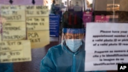 FILE - A test specialist works at a COVID-19 testing site in Los Angeles, Dec. 9, 2020. A lab in Minnesota confirmed Monday the first U.S. case associated with the variant originally seen in Brazil.