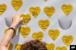COVID-19 survivors gather at City Hall Park and place stickers representing lost relatives on a wall Aug. 7, 2021, in New York, as part of the largest nationwide day of awareness and action for COVID-19 survivors.