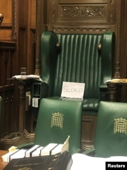 """A piece of paper with the word """"silenced"""" sits on the British Parliament speaker's chair at the House of Commons, in protest of the House's suspension, in London, Sept. 10, 2019."""