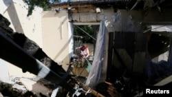 Warga memeriksa rumahnya di Donetsk, Ukraina timur yang hancur akibat serangan artileri bulan lalu. Konflik di Ukraina timur telah memasuki tahun keenam.