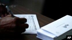 Presiden Dewan Kota Philadelphia Darrell L. Clarke mengisi formulir permohonan pengiriman surat suara lewat pos di Temple University in Philadelphia, 29 September 2020.