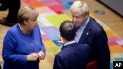 Kanselir Angela Merkel berbicara dengan PM Inggris Boris Johnson (kanan) dan Presiden Perancis Emmanuel Macron pada KTT Uni Eropa di Brussels, Belgia (foto: dok).