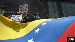 """Activistas sostienen un cartel que dice """"vacunas para todos"""" y una bandera gigante venezolana durante una protesta para exigir que todos los trabajadores de la salud sean vacunados contra el COVID-19, en Caracas, el 17 de abril de 2021."""