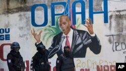 La policía pasa frente a un mural que muestra al presidente haitiano Jovenel Moise, cerca de la residencia del líder donde fue asesinado por hombres armados en Puerto Príncipe, Haití, el miércoles 7 de julio de 2021.