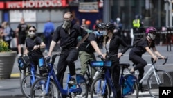 Cyclists wearing protective masks ride through Times Square, Saturday, April 25, 2020, in New York. New York is starting to test healthcare workers for coronavirus antibodies and will do the same next week with transit and law enforcement workers as…
