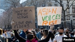 FILE - A woman holds up signs during a Rally Against Hate to end discrimination against Asian Americans and Pacific Islanders in New York City, March 21, 2021.