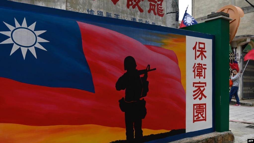 资料照:一名游客从台湾金门岛一座绘有中华民国国旗的墙壁前走过。