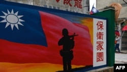FILE - A tourist (R) walking past a mural painted on a wall on Taiwan's Kinmen islands, which lie just 3.2 kms (two miles) from the mainland China coast (in background) in the Taiwan Strait, Oct. 21, 2020.