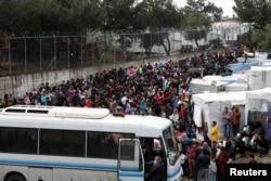FILE - Migrants from the Moria camp wait to board busses to the port from where they will be transferred to the mainland as a precaution against the spread of the coronavirus disease (COVID-19) outbreak, on the island of Lesbos, Greece, May 3, 2020.
