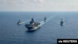 Kapal pengawal milik angatan laut Australia yang dilengkapi dengan peluru kendali HMAS Parramatta (FFH 154) (kiri) berlayar bersama kapal perang milik angkatan laut AS dalam sebuah patroli di laut China Selatan pada 18 April 2020. (Foto: U.S. Navy via Reuters)