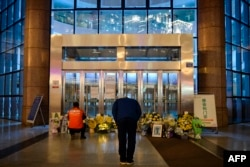 FILE - A man bowing in front of flowers and a photo of the late ophthalmologist Li Wenliang outside the Houhu Branch of Wuhan Central Hospital in Wuhan in China's central Hubei province, Feb. 7, 2020.