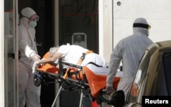 FILE - A patient is carried on a stretcher from a nursing home to a hospital, as the spread of the coronavirus disease (COVID-19) continues, in Rome, Italy, May 2, 2020.