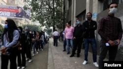 2020年11月7日,埃及男子和妇女分别在埃及首都开罗一个设立了投票站的学校外排队参加埃及议会第二轮选举。