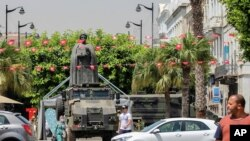Tunisians walk past a military armored personnel carrier at Habib Bourguiba Avenue July 30, 2021.