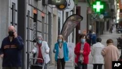 Des personnes portant des masques faciaux pour se protéger contre le coronavirus marchent dans les rues de Madrid, Espagne, le 13 mai 2020.