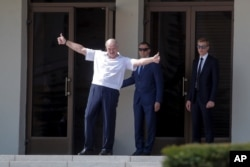 Belarusian President Alexander Lukashenko gestures as he greets his supporters gathered at Independent Square of Minsk, Belarus, Aug. 16, 2020.