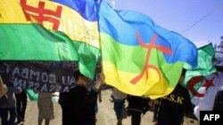 FILE - Demonstrators wave Berber flags in Agouni Arouss, Algeria, April 18, 2002. Suspected members of MAK, a group seeking independence for the Berber-speaking Kabylie region, were arrested after attacks in Algeria, police said Sept. 6, 2021.
