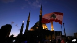 Anti-government protesters wave Lebanese flags and chant slogans during ongoing protests against the Lebanese government, in Beirut, Feb. 1, 2020.