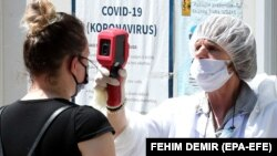 A medical staff attends to people as they arrive to test for coronavirus, at a hospital in Sarajevo, Bosnia and Herzegovina, 01 July 2020.